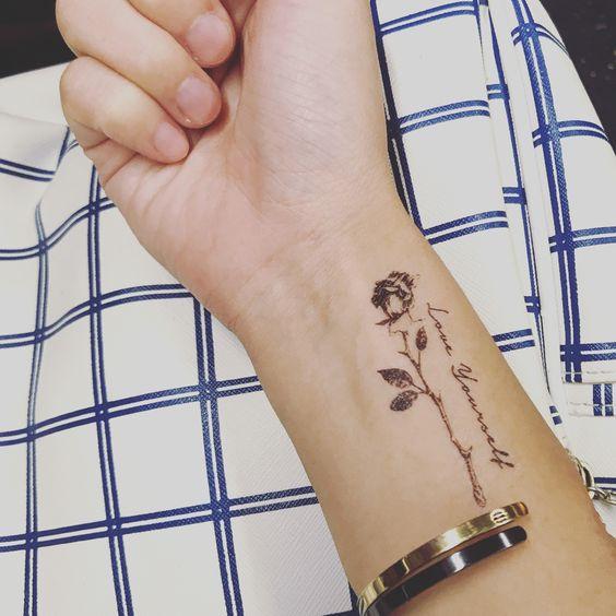 black small flower tattoo on side wrist for girl