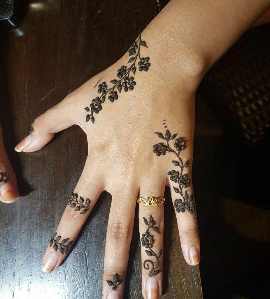 flower tattoo mehndi design on finger and hand