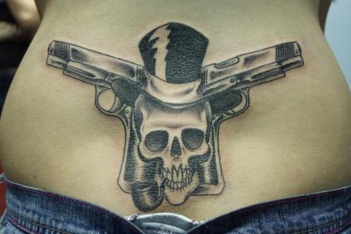 gun cross tattoo with skull design for women