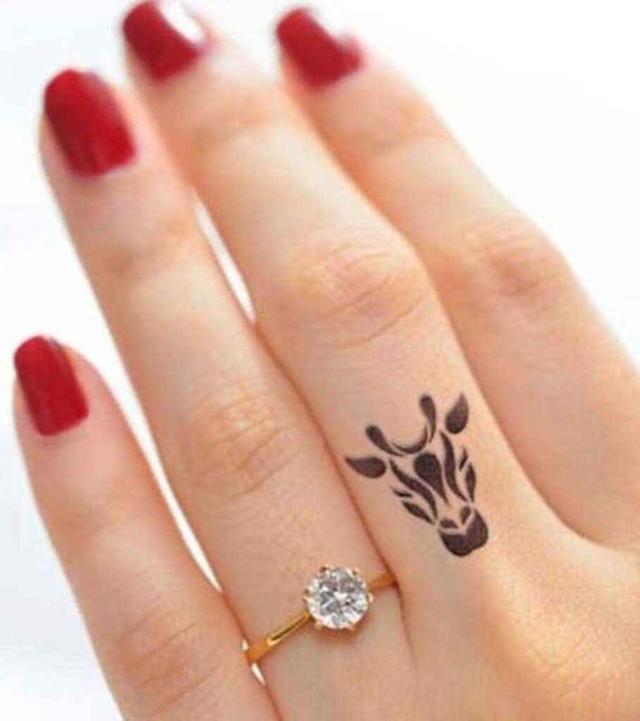small cow symbol tattoo on female finger picture