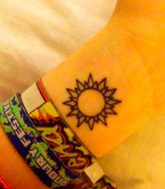 realistic sun tattoo on wrist