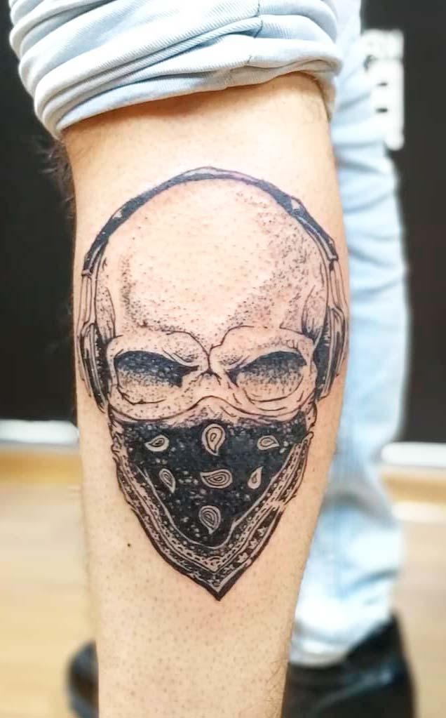 man with skull tattoo on legs