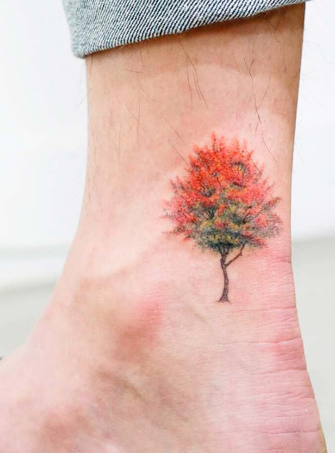 tiny tree tattoo with color design on leg